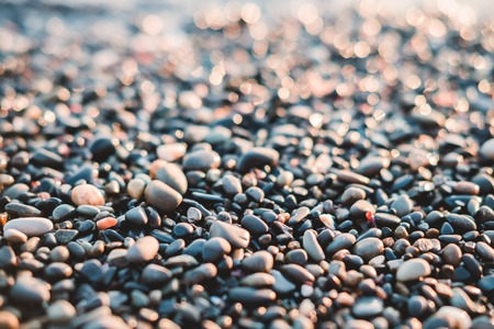 Small stones by the sea with bokeh effect. Blurred decorative vacation and holiday