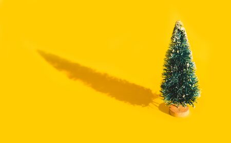 Miniature toy artificial Pine tree on wooden base on bright yellow Christmas background with long shadow. Concept of New Year, Christmas holiday greeting card.