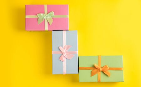 Gift box on sunny yellow background. The concept of the New Year, Christmas, Birthday, Anniversary. Top view. Flatlay. Stok Fotoğraf