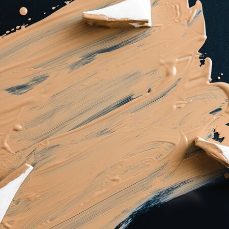 Texture of liquid foundation on dark surface with sponges for applying a tone. Cosmetics advertising concept.