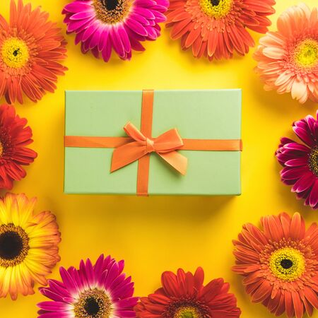 Gift box with bright beautiful gerbera flower on sunny yellow background. The concept of the New Year, Christmas, Birthday, Anniversary. Top view. Flatlay. Stok Fotoğraf