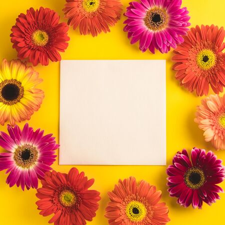 Bright beautiful gerbera flowers and paper card on a sunny yellow background. Mothers Day, Valentine holiday. Place for text, lettering or product. View from above, Copy space. Flatlay.