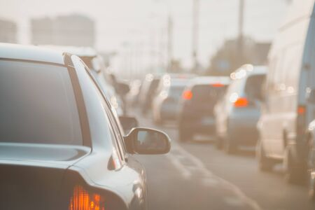 The back of an unknown car at sunset on road in heavy traffic. Stock Photo