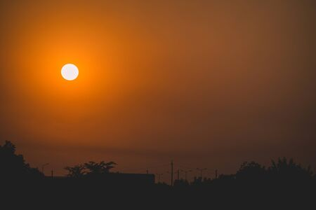 Orange sun at sunset on background of black silhouette of trees and houses. Stock Photo