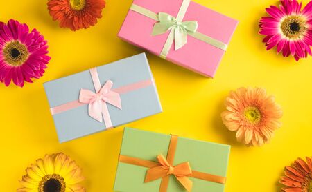 Gift box with bright beautiful gerbera flower on sunny yellow background. The concept of the New Year, Christmas, Birthday, Anniversary. Top view. Flatlay. Stock Photo