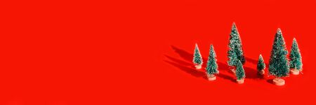 Miniature toy artificial Pine tree on wooden base on bright red Christmas background with long shadow. Concept of New Year, Christmas holiday greeting card.