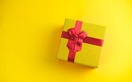 Gift box on sunny yellow background. The concept of the New Year, Christmas, Birthday, Anniversary. Top view. Flatlay. Stock Photo