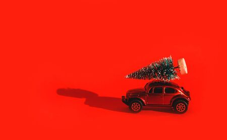 Miniature toy artificial Pine tree on wooden base and red car, bright red Christmas background with long shadow overlay. Concept of New Year, Christmas, greeting card. Stock Photo