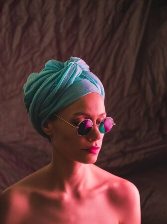 Portrait of girl in neon light, dressed in blue turban on her head and green glasses. Stock Photo
