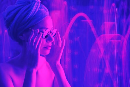 Portrait of girl in neon light, dressed in blue turban on her head and green glasses. Stock Photo - 129062561
