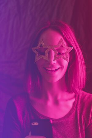 Girl neon light, dressed in glasses for party in form of stars, takes selfie on the phone. Stock Photo - 129062557