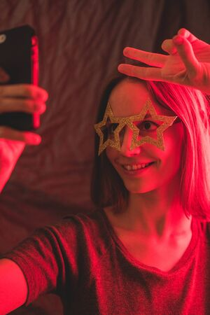 Girl neon light, dressed in glasses for party in form of stars, takes selfie on the phone. Stock Photo - 129062583