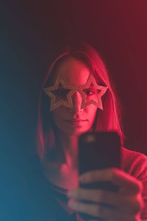 Girl neon light, dressed in glasses for party in form of stars, takes selfie on the phone. Stock Photo - 129062582