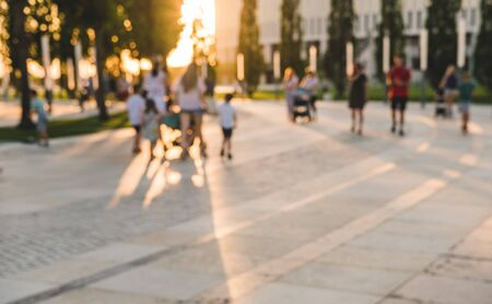 Blurred background with long shadows from trees in park. Silhouettes of unrecognizable people walking in park. Stock Photo
