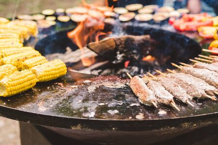 Round barbecue grill with open fire inside. Meals for summer picnic are being prepared: corn, eggplant, bell pepper, kebab. Stock Photo - 129062588