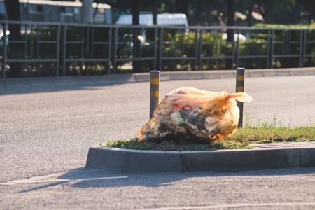 Garbage plastic bag lying on the side of road. oncept of environmental problems. Banco de Imagens