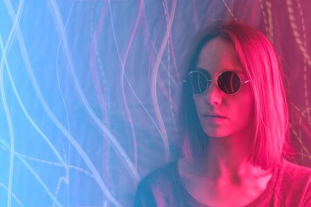 Girl in neon light on dark background, dressed in green glasses. Banco de Imagens