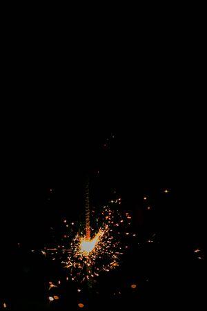 Burning bengal light sparkler on a dark black background. Stock Photo