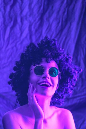 Fashion girl in neon light, dressed in an afro wig on her head and green glasses. Stock Photo