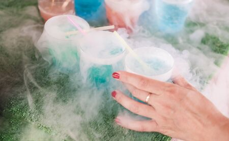 Steaming multi-colored cocktails with dry ice standing on green background. Female hand takes one cocktail.
