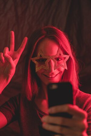 Girl neon light, dressed in glasses for party in form of stars, takes selfie on the phone.