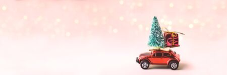 Toy car with Christmas tree and gift on roof. Background of blurred bokeh from garland. New Year and Christmas holiday concept.