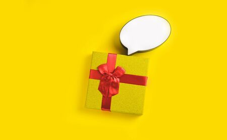 Golden gift box with white bubble speech on sunny yellow background. The concept of the New Year, Christmas, Birthday, Anniversary. Top view. Flatlay. Stock Photo