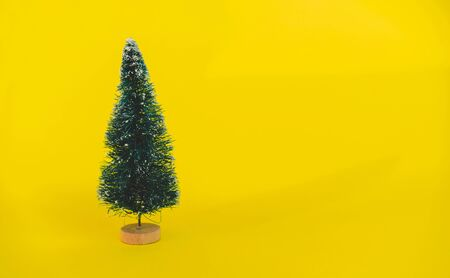 Miniature toy artificial Pine tree on wooden base on bright yellow Christmas background with long shadow. Concept of New Year, Christmas holiday greeting card. Banco de Imagens - 129062698