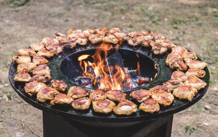 Round barbecue grill with open fire inside. Meals for summer picnic are being prepared: chicken pieces.