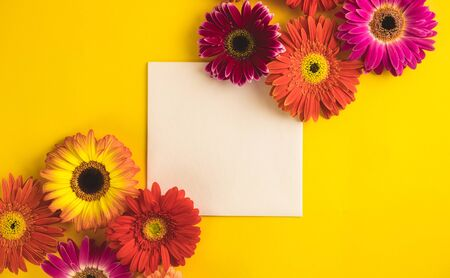Bright beautiful gerbera flowers and paper card on a sunny yellow background. Mothers Day, Valentine holiday. Place for text, lettering or product. View from above, Copy space. Flatlay. Stock Photo - 129062707