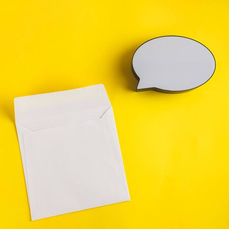 Bubble text speech empty and paper card on sunny yellow background. Place for text, lettering or product. View from above, Copy space. Flatlay.