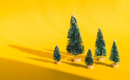 Miniature toy artificial Pine tree on wooden base on bright yellow Christmas background with long shadow. Concept of New Year, Christmas holiday greeting card. Stock Photo - 129062708
