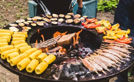 Round barbecue grill with open fire inside. Meals for the summer picnic are being prepared: corn, eggplant, bell pepper, kebab. Male hands in black gloves turn the food over with barbecue tongs.