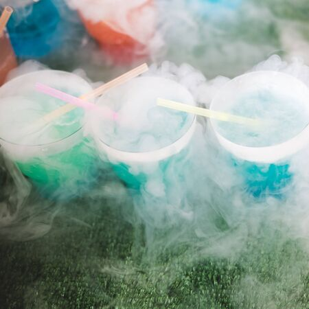 Steaming multi-colored cocktails with dry ice standing on green background.