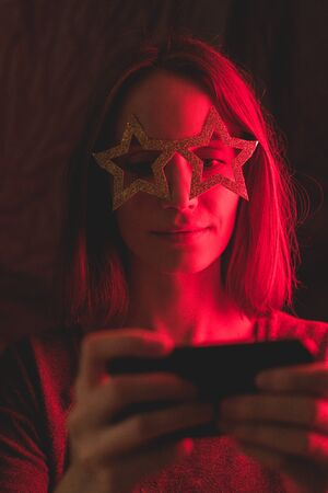 Girl neon light, dressed in glasses for party in form of stars, takes selfie on the phone