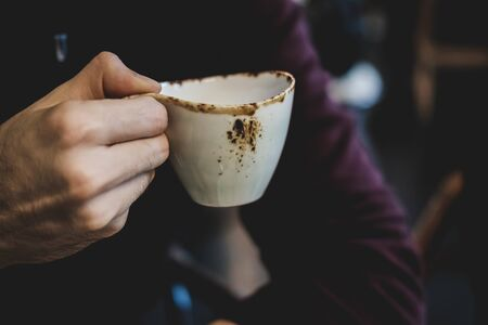 Male hand in burgundy sweater holds cup of coffee or tea in cafe