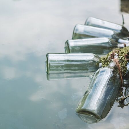 Bottles connected with notes inside float by the lake. Quests, games, adventures