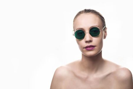 Fashion girl model in green sunglasses isolated on white background looking at the camera. Studio shot Banco de Imagens