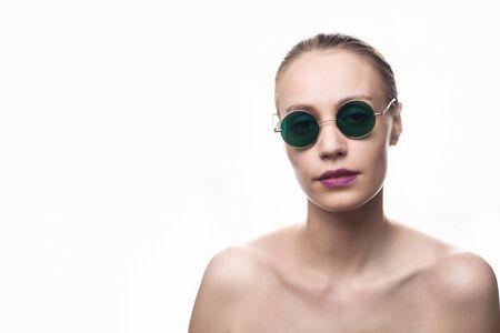 Modemädchenmodell in der grünen Sonnenbrille lokalisiert auf weißem Hintergrund, der die Kamera betrachtet. Studioaufnahme
