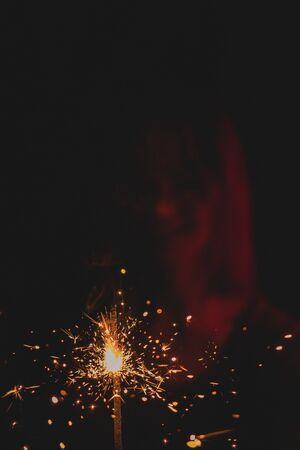 Girl in neon light on dark dressed in green glasses, holds a burning sparkler front of her Banco de Imagens