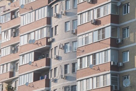 Close-up. High-rise windows with air conditioning and balconies. The concept of overpopulation of planet