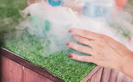 Steaming multi-colored cocktails with dry ice standing on green