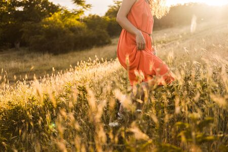 Beautiful young girl with dark curly hair in bright orange dress walks through an autumn forest or field at sunset. Banco de Imagens