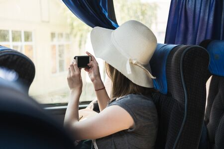 Young woman tourist in hat sits on a bus and takes a selfie on the phone