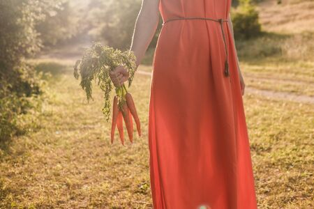 Beautiful young girl with dark curly hair in a bright orange dress is holding a bunch of carrots. Harvest concept autumn