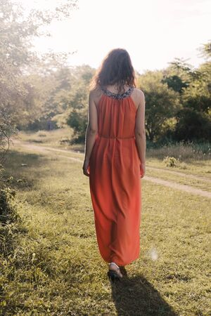 Beautiful young girl with dark curly hair in bright orange dress walks into the distance through forest or field at sunset.