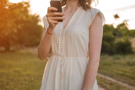 Beautiful young woman with brown hair in white dress walks through the autumn or summer forest with smartphone in her hand.