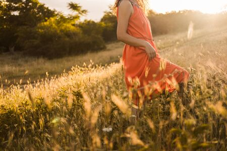 Beautiful young girl with dark curly hair in bright orange dress walks through the autumn or summer forest or field at sunset. Banco de Imagens
