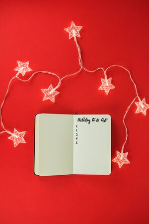Notebook for wish list, goals or promises for New Year on red background and garland in form of stars. Concept of to-do list. New life from new year. Top view. Flat lay. Copy space.