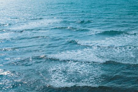 Texture of the sea or ocean with white lamb waves rolling to the shore